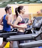 Bir spor merkezinde bir koşu bandı üzerinde çalışan sağlıklı çift — Stok fotoğraf