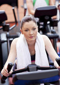 Serious athletic woman pedaling during a training in a sport cen — Stock Photo