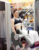Portrait of a serious woman using a leg press in a sport centre — Stock Photo