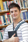 Portrait of a smart student holding a book standing in the libra — Stock Photo