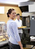 Attractive woman buying baguette in a cafeteria with baker in th — Stock Photo