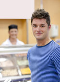 Portrait of a cheerful man choosing his lunch in the cafeteria — Stock Photo
