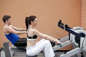 Jovem casal usando um remador em um centro de desporto — Foto Stock