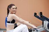 счастливая женщина со своим парнем, с помощью гребец в фитнес-центре — Стоковое фото