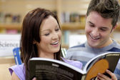 Cheerful couple reading a book in the science department of a bo — Stock Photo