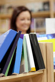 Close-up of a book shelf in a library with female customer in th — Stock Photo