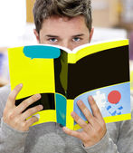 Male student standing in a book shop hiding his face behind a bo — Stock Photo