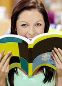 Portrait of a beautiful woman holding a book in a library smilin — Stock Photo