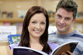 Portrait of a cute couple reading a book in a shop — Stock Photo
