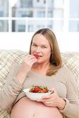 Serious future mom eating strawberries sitting on the sofa — Stock Photo