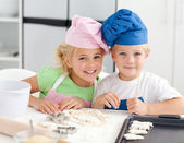 Portrait of two adorable children baking in the kitchen — Stock Photo