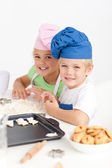 Adorable siblings kneading together a dough in the kitche — Stock Photo