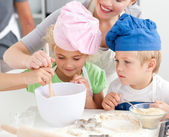 Two children and their mother stiring a preparation for cookies — Stock Photo
