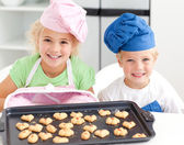 Happy little brother and sister with their biscuits ready to eat — Stock Photo