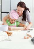 Beautiful mother and her cute daughter using a rolling pin — Stockfoto