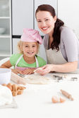 Portrait of a happy mother and daughter kneading a dough — Stock Photo
