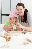 Happy girl with her mother baking little cakes — Stock Photo