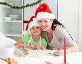 Portrait of a cute girl with her mother baking Christmas cookies — Stock Photo