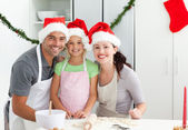Portrait of a man with wife and daughter cooking Christmas biscu — Stock Photo