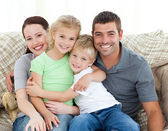 Adorable family sitting on the sofa and smiling — Stock Photo