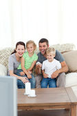 Happy family laughing while watching television sitting on the s — Stock Photo