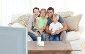 Adorable family watching television together sitting on the sofa — Stock Photo