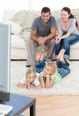 Adorable siblings watching television with their parents lying o — Stock Photo