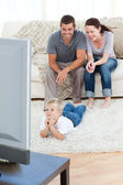 Cute little boy watching television on the floor with his parent — Stock Photo