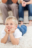 Cute little boy lying on the floor and watching television with — Stock Photo