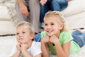Brother and sister watching television on the floor with their p — Stock Photo