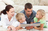Family looking at a book on the floor — Stock Photo