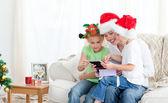Matka a děti při pohledu na kalendář, který sedí na pohovce — Stock fotografie