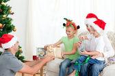 Šťastný otec dává dárek k jeho dceři sedí na sof — Stock fotografie
