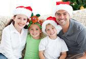 šťastná rodina s vánoční čepice sedí na pohovce — Stock fotografie