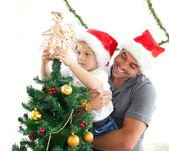 Happy father helping his son to put an angel on the Christmas tr — Stok fotoğraf