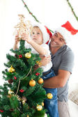 Father and son decorating their christmas tree — Стоковое фото