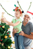 Happy father helping his daughter to put an angel on the Christm — Foto Stock