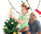 Cute little girl decorating the christmas tree with her father — Stok fotoğraf