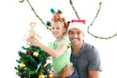 Happy father and daughter decorating together the christmas tree — Stok fotoğraf