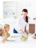Adorable mother serving salad to her children for lunch — Stock Photo