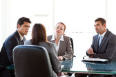 Rear view of a businesswoman being interviewed by three executiv — Stock Photo