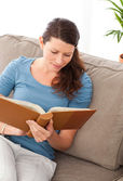 Attentive woman reading a book sitting on her sofa — Stock Photo