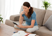 Anxious woman calculating her debts sitting in the living-room — Foto Stock