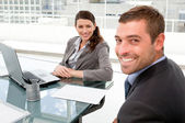 Happy businesspeople working together on a laptop during a meeti — Stock Photo