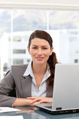 Smiling businesswoman on the computer looking at the camera — Stock Photo