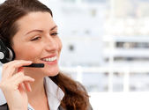 Smiling businesswoman talking on the phone with headphones — Stock Photo