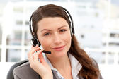 Pretty businesswoman with earpiece and looking at the camera — Stock Photo