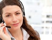 Pretty businesswoman with earpiece smiling at the camera — Stock Photo