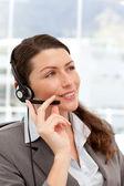 Pensive businesswoman talking on the phones using headphones — Stock Photo