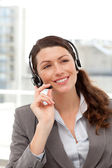Cheerful businesswoman using earpiece sitting at her desk — Stock Photo